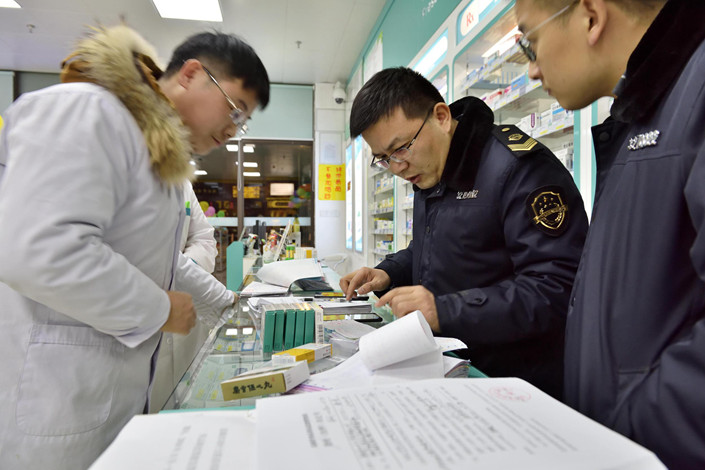Law enforcement officers check purchase certificates and the quality of drugs at a pharmacy in East China's Jiangsu province on Jan. 29. Photo: VCG