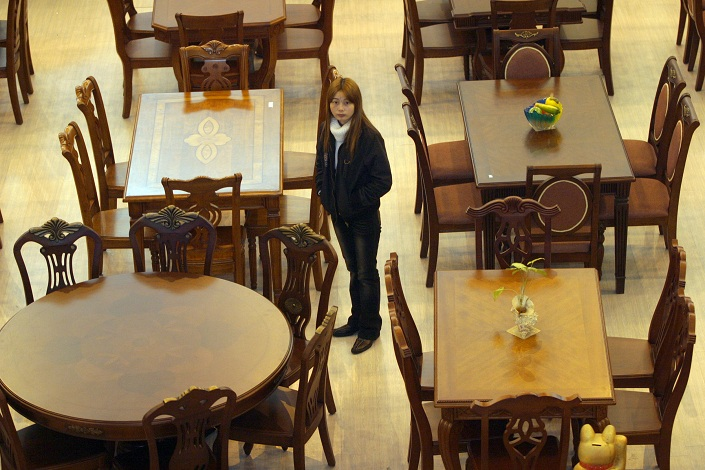 A shopper looks at dining table sets at a furniture exhibition center in the southern city of Lecong. Photo: Bloomberg