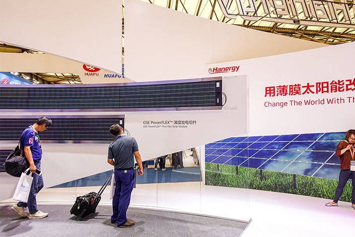Visitors stop to examine the Hanergy booth at an exhibition in Shanghai on May 28. Photo: VCG