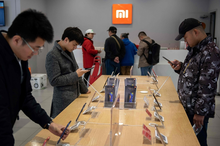 Customers check out mobile phones in a Xiaomi store on Nov. 7 in Beijing. Photo: VCG