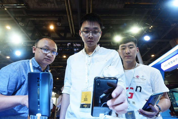 People try out a 5G-enabled Xiaomi phone at a tech fair in Hangzhou on May 31,2019. Photo: VCG