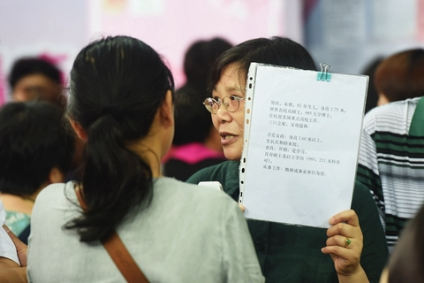 A mother holds up a sheet of paper with her son's personal details printed on it. Photo: VCG