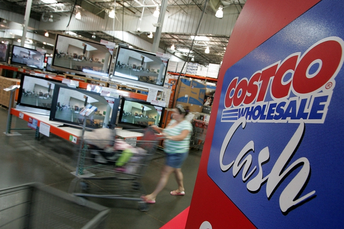 A customer pushes her shopping cart by a display of televisions at a Costco store on July 13, 2007, in Richmond, California. Photo: VCG