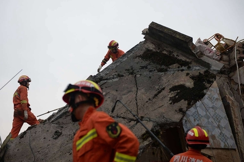 Rescuers search through rubble. Photo: VCG