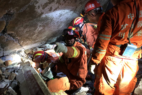 Rescuers try to find people buried under collapsed buildings. Photo: VCG