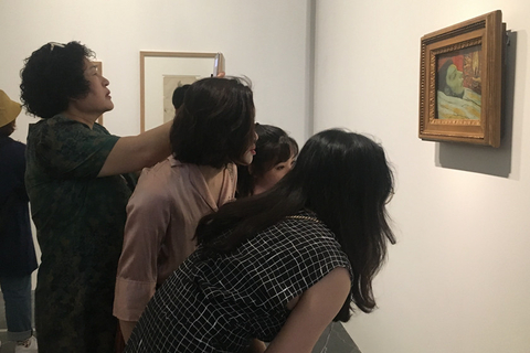 A visitor to the exhibit snaps a photo of one of Picasso's paintings on Tuesday. Photo: Caixin