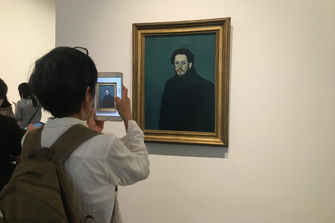 A visitor takes a photo of a Picasso portrait on Tuesday. Photo: Caixin