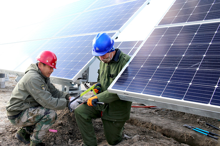 Workers install solar panels at a photovoltaic power station in Daqing, Northeast China's Heilongjiang province, in March 2018. Photo: IC Photo