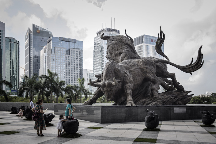 People stand in front of a sculpture of bulls at the entrance to the Shenzhen Stock Exchange building in Shenzhen. Photo: Bloomberg