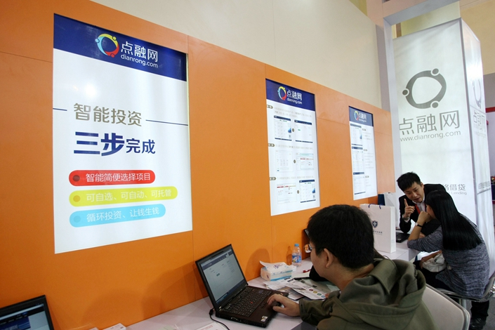 People visit the booth of P2P lender Dianrong during an exhibition in Shanghai in November 2013. Photo: IC Photo