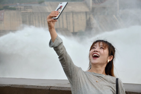 A visitor takes a selfie in front of the surging water. Photo: IC Photo