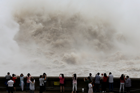 Visitors snap photos Friday of the water released from the Xiaolangdi Reservoir into the Yellow River in Luoyang, Central China's Henan province. Photo: VCG