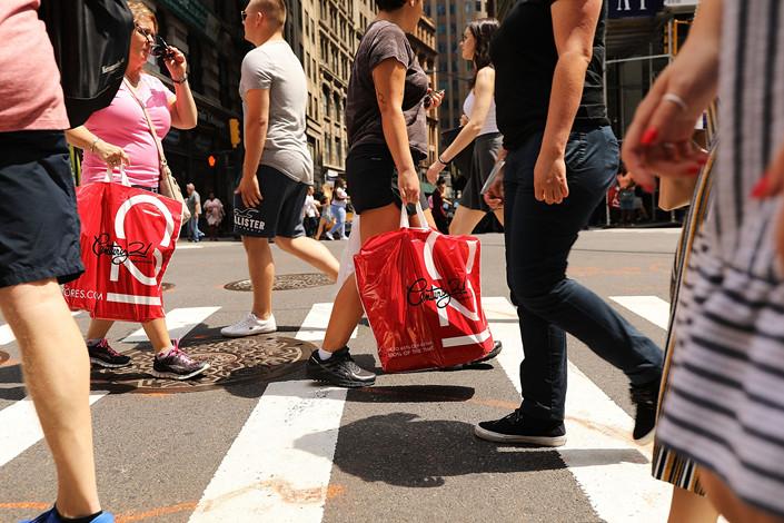 People walk along Broadway in lower Manhattan on July 27, 2018. Photo: VCG