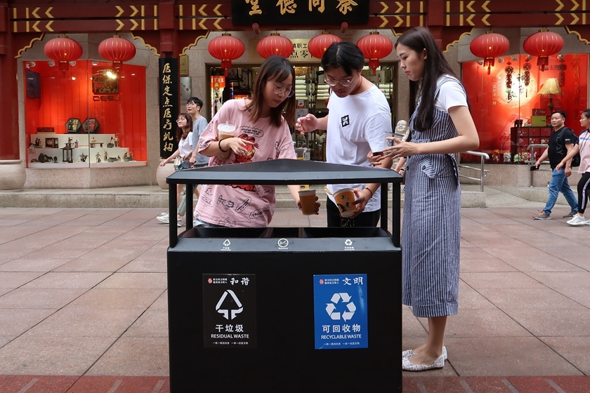Visitors sort garbage on the street in Shanghai on Monday. Photo: VCG