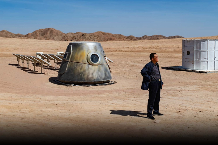 A man stands by space artifacts at Mars Base 1 in Jinchang, Gansu province on April 17. Photo: Matjaz Tancic for Sixth Tone