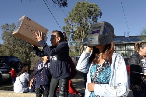 People look through hand-made devices to view the eclipse in La Paz, Bolivia, on Tuesday. Photo: VCG