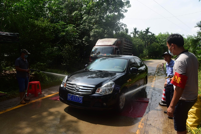 Disease prevention staffers spray disinfectant on a passing car in Qionghai, South China's Hainan province, on May 22, in an effort to contain the spread of African swine fever. Photo: VCG