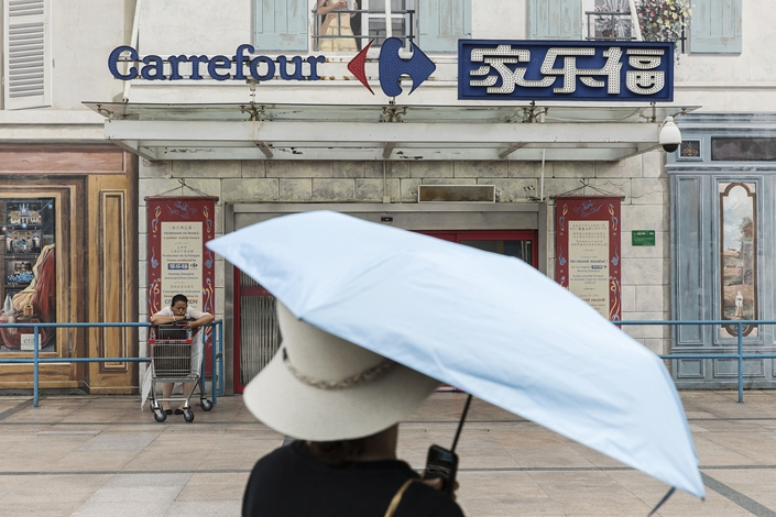 A pedestrian walks past a Carrefour supermarket in Shanghai on June 24. Photo: VCG