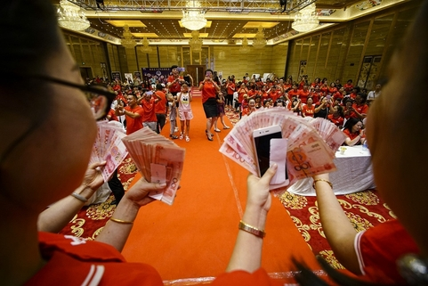 Weishang sellers hold out their bonuses at an annual party for the app's top sellers. Photo: VCG