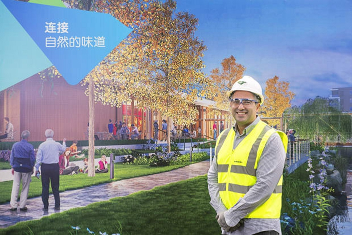 Lendlease's Tony Lombardo in front of a render of the retirement village. Photo: AFR