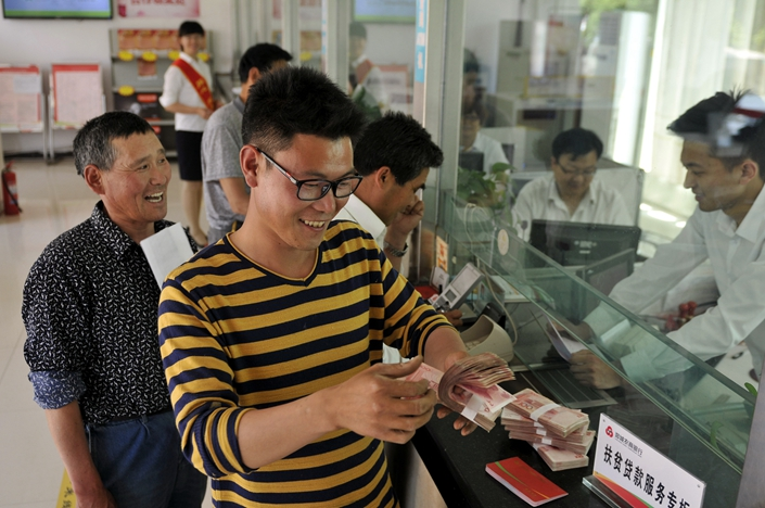 A farmer recieves a poverty alleviation loan at a bank in Linyi, Shandong province, on May 5. Photo: IC Photo