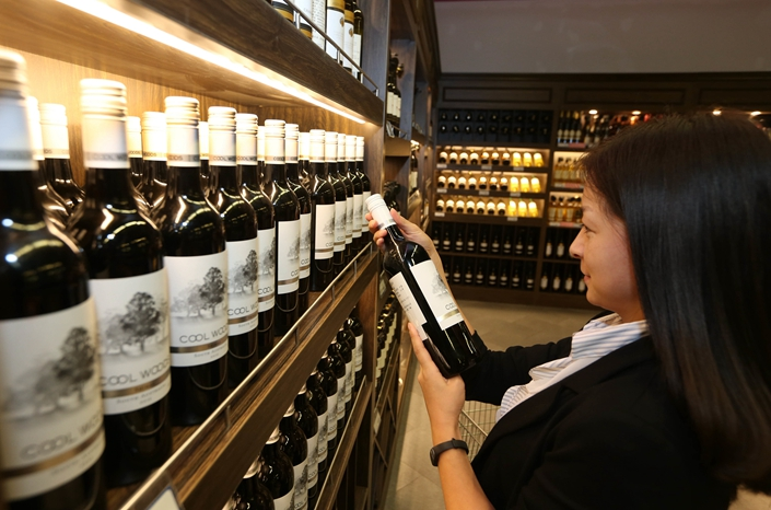 A customer shops for bottled wine imported from Australia in Nantong city, East China's Jiangsu province, 17 June, 2018. Photo: IC Photo