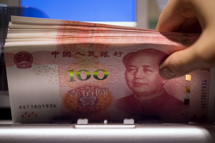 One hundred-yuan Chinese banknotes pass through a currency counting machine