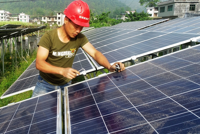 Technicians install solar panels in Xiaogang village, Chongqing on May 3. Photo: IC Photo