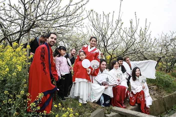 Tourists take photos among flowers in Jiaxing, Zhejiang province on March 31. Photo: IC Photo