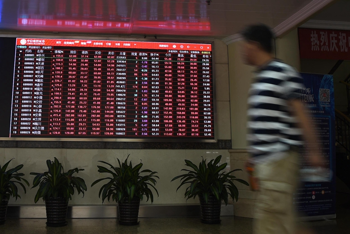 An investor walks past a display showing market movements at a securities trading department in Beijing on July 22. Photo: VCG