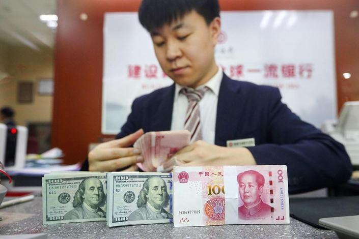 The onshore yuan depreciated beyond 7 per dollar soon after trading began Monday, something it has not done since April 2008. Photo: VCG