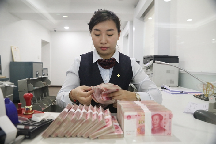 Bank workers count money at a bank in Harbin, Northeast China's Heilongjiang province on April 9. Photo: VCG