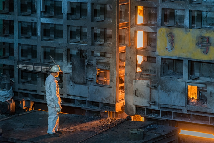 A steelworker stands next to a smelting furnace in Panzhihua, Sichuan province, on Aug. 25, 2018. Photo: VCG