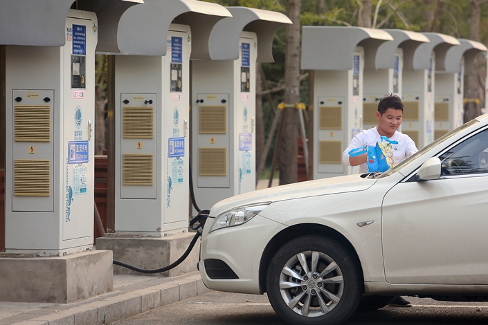 The owner of an electric car charges his vehicle at a charging station in Beijing in October 2018. Photo: VCG