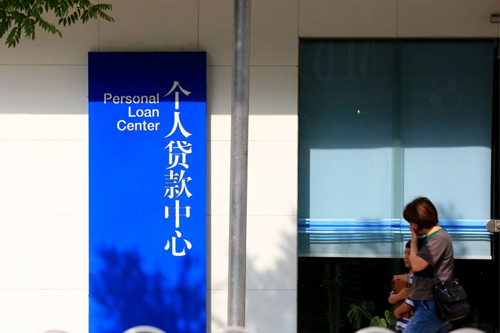 Residents walk past a bank's personal loan center on June 30 in Huai'an, East China's Jiangsu province. Photo: IC Photo