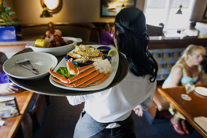 A waitress carries a tray with a lobster kettle and a crab trio at a Red Lobster seafood-restaurant chain location in Yonkers