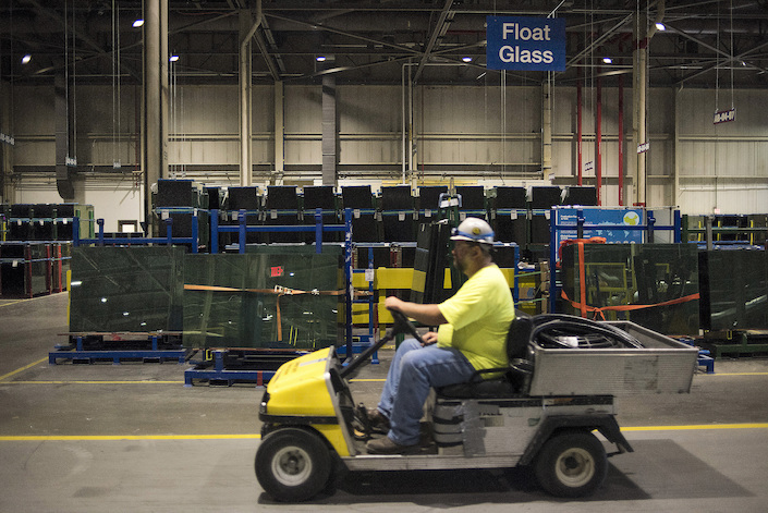An employee drives a utility car past the float glass packaging area at the Fuyao Glass America production facility near Dayton, Ohio. Photo: Bloomberg