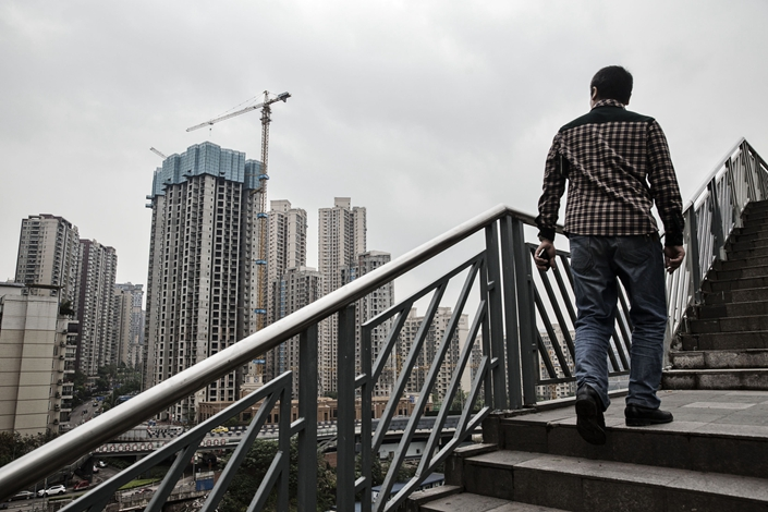 A pedestrian walks up a flight of stairs in front of residential buildings under construction in Chongqing, China, on Thursday, April 14, 2016. Photo: Bloomberg