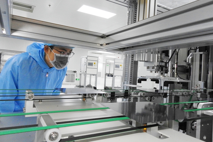 A worker inspects the production line for high-efficiency black silicon solar cells on July 11 in Lianyungang, East China's Jiangsu province. Photo: VCG
