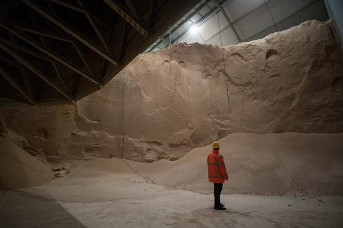 An employee looks at soybean meal produced by Glencore PLC as it is stored before transportation at the Port of Rotterdam, Netherlands, on April 25, 2017. Photo: Bloomberg