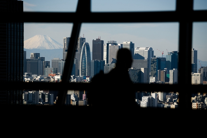 Mount Fuji stands behind buildings as a visitor looks out at the skyline from an observation deck in Tokyo on Jan. 11. Photo: Bloomberg