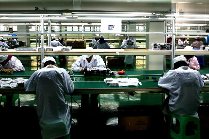 Workers assemble electronics at a factory in Huaying, Sichuan province, on Nov. 11, 2018. Photo: VCG