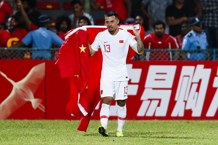 Nico Yennaris, or Li Ke as he is known in China, drapes himself in the Chinese flag on Sept. 10 during a World Cup qualifier match in the Maldives.  Photo: VCG