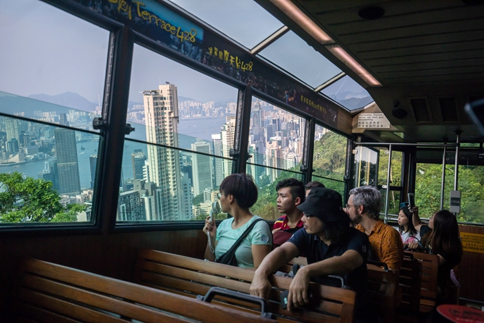 Passengers look towards the Hong Kong's skyline as they ride onboard the Peak Tram on Aug. 28, 2019. Photo: Bloomberg