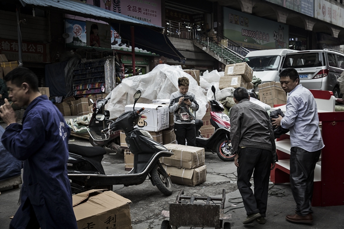 A woman uses a smartphone as workers move boxes at a street market in Chongqing on April 12, 2016. Photo: Bloomberg
