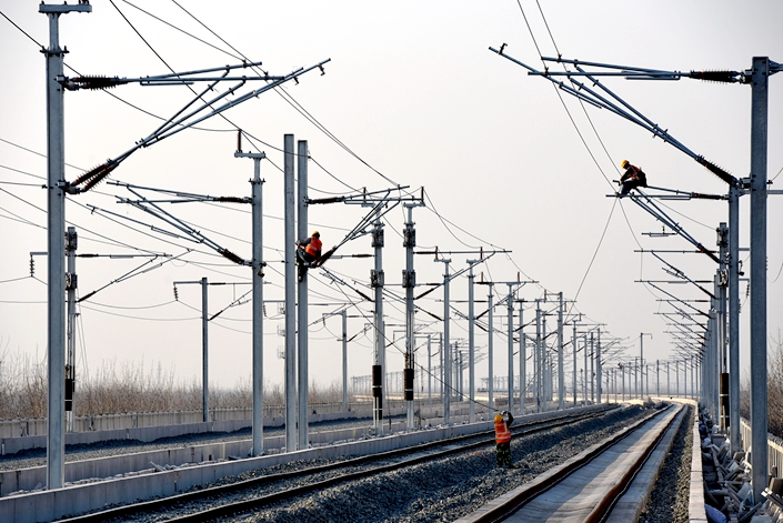 Workers install power lines on a railway line in East China's Jiangsu province on March 15. Photo: VCG