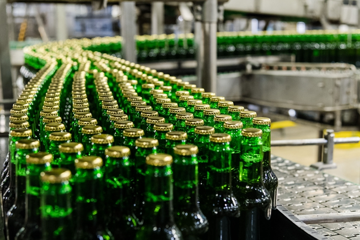 Sealed green Stella Artois lager beer bottles pass along a conveyor at the Anheuser-Busch InBev NV brewery in Leuven, Belgium, on July 17, 2019. Photo: Bloomberg