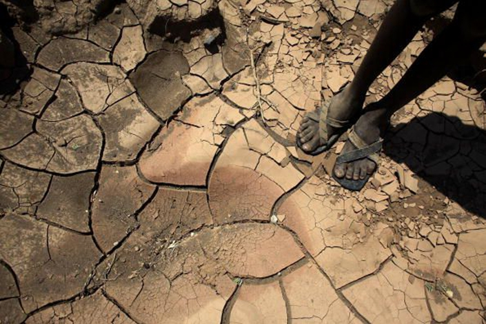 A young boy from the Turkana tribe in Northern Kenya stands on a dried up river bed on Nov. 9, 2009 near Lodwar, Kenya. Photo: Bloomberg