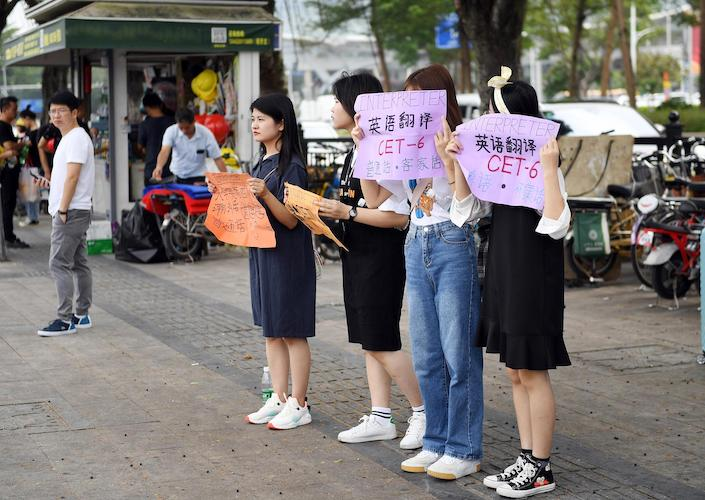 College students seeking interpreter jobs at the Canton Fair hold signs outside the Guangzhou International Convention and Exhibition Center on Oct. 14, 2019. Photo: VCG
