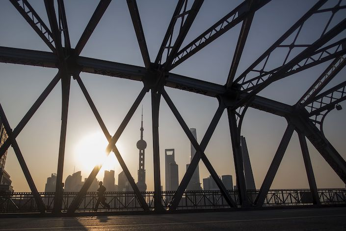 =A jogger runs across a bridge on his morning exercise during sunrise at the promenade on the Bund along the Huangpu River